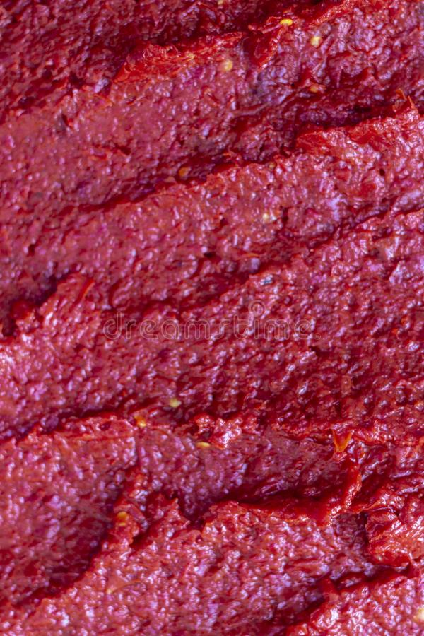 Vertical close-up front detail shot of juicy tomato paste. Beautiful shoot under sunset royalty free stock images
