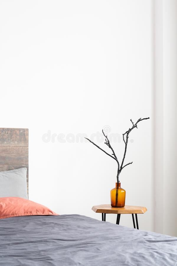 Vertical close-up of glass orange vase with a tree branch standing on a simple wood table next to the bed. Vertical close-up of glass orange vase with a tree royalty free stock photo