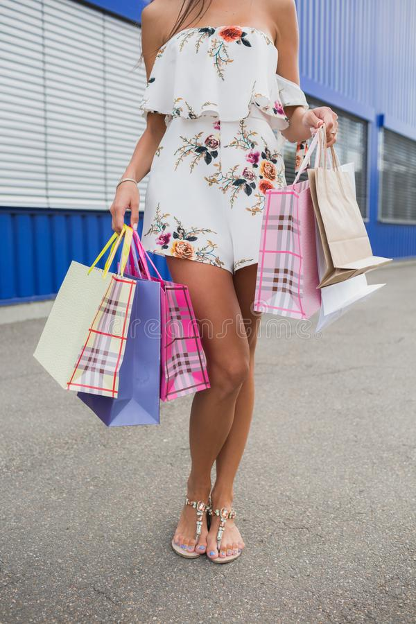 Vertical close-up photo of stunning legs on shopping, standing with colorful shopping bags, shopping concept. royalty free stock photos