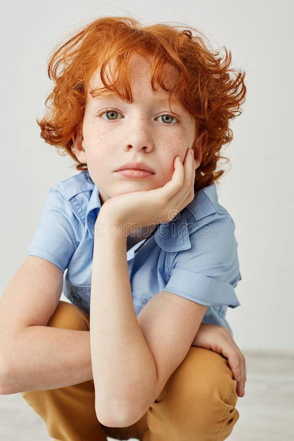 Vertical close up shot of funny boy with orange hair and freckles, holding head with hand, looking in camera with calm stock images