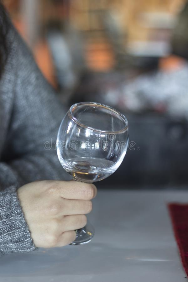 Vertical close-up shot for woman holds empty wine glass with blurry background in Izmir at Turkey for winter season. At sunset royalty free stock images