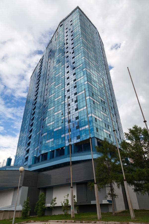 Vertical close-up on a tall building with mirrored windows which reflects a sky with clouds. Business and construction stock image