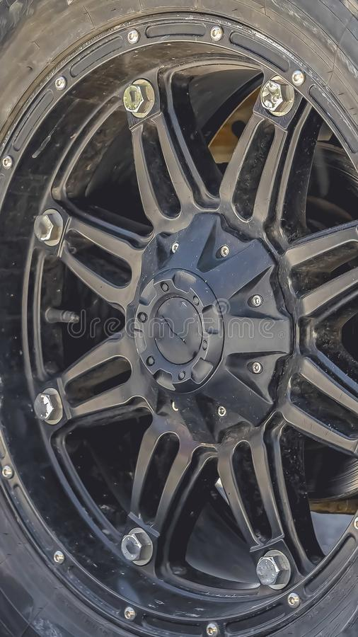 Vertical Close up view of the black rubber wheel of a vehicle parked on a sunlit road royalty free stock images