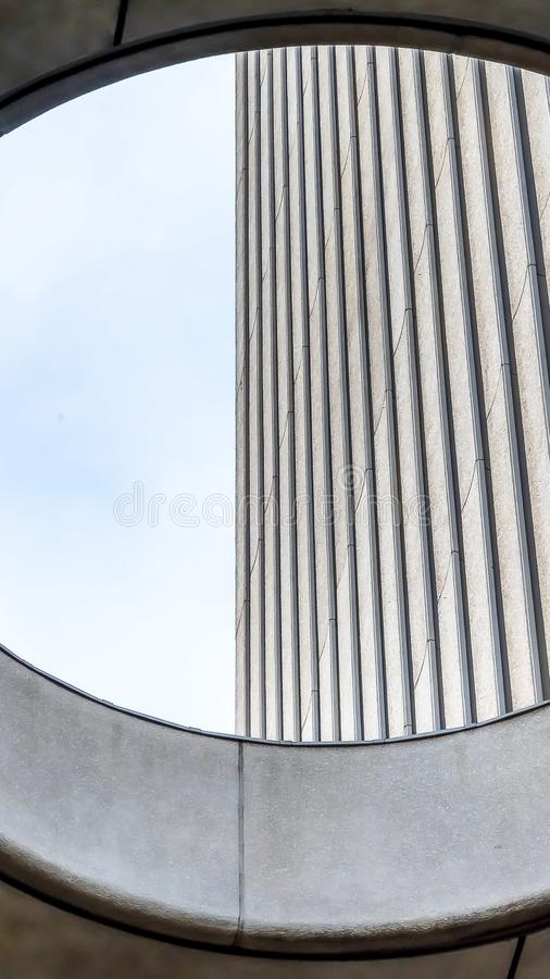 Vertical Close up view from the inside of the round skylight of a building. Corrugated concrete wall and bright sky can be seen through the hole royalty free stock images