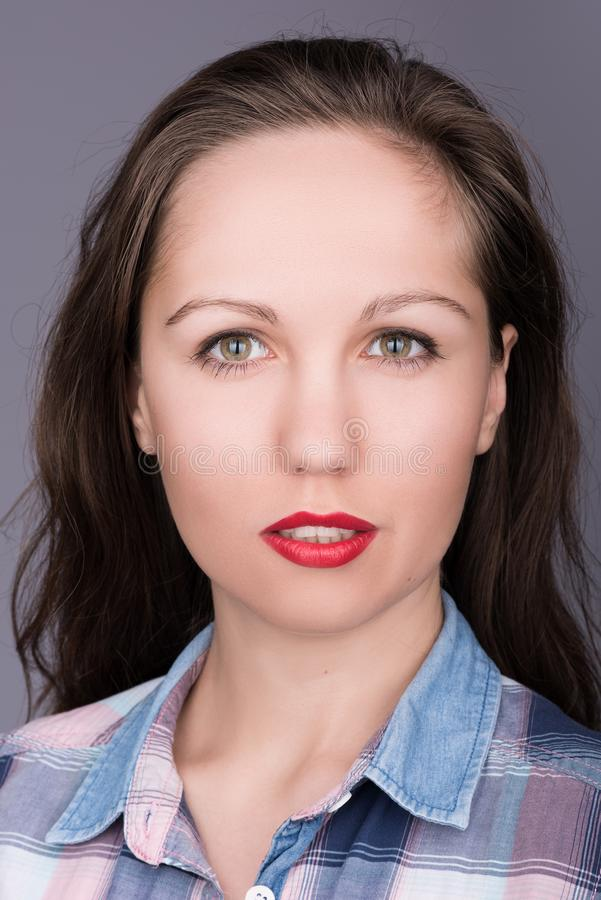 Vertical closeup portrait of a beautiful young woman with flowing hair and red lipstick royalty free stock photography