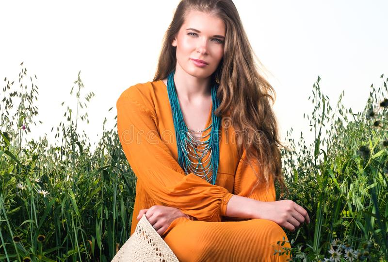 Vertical closeup portrait of young woman sitting in tall grass stock photos