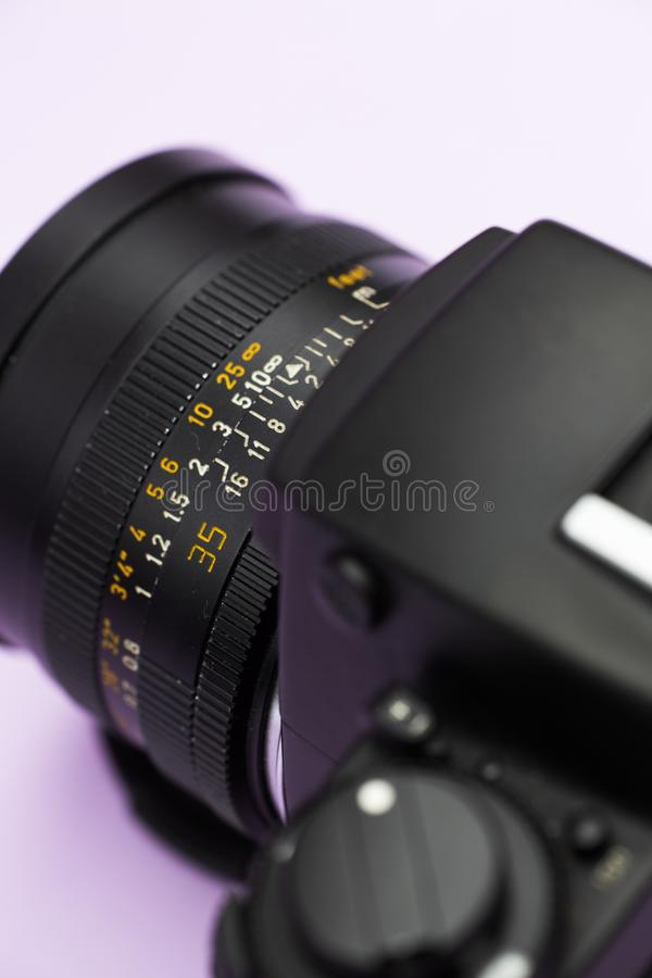 Vertical closeup shot of a camera on a white surface royalty free stock images