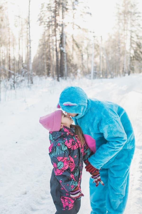 Vertical closeup shot of a cute little girl kissing a female in a fluffy blue costume stock photo