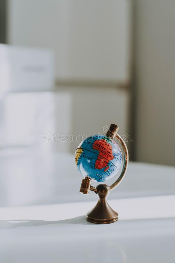Vertical closeup shot of a decorative small globe on a white desk and blurred background. A vertical closeup shot of a decorative small globe on a white desk and royalty free stock photo