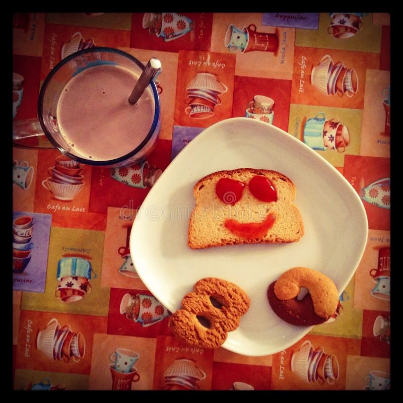 Overhead shot of delicious breakfast with cookies, smily jam on bread and chocolate milk stock image