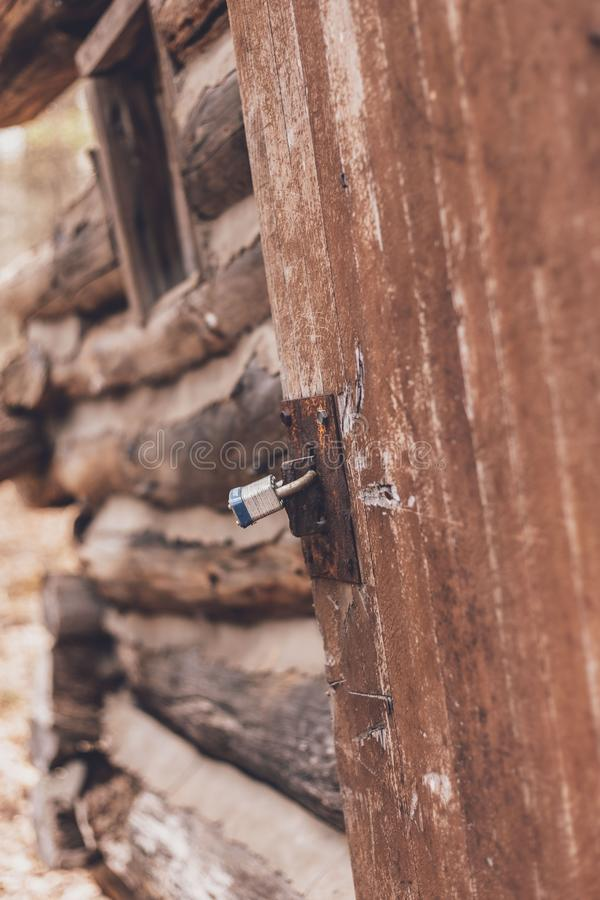 Vertical closeup shot of a gray lock on a wooden door. A vertical closeup shot of a gray lock on a wooden door royalty free stock photos
