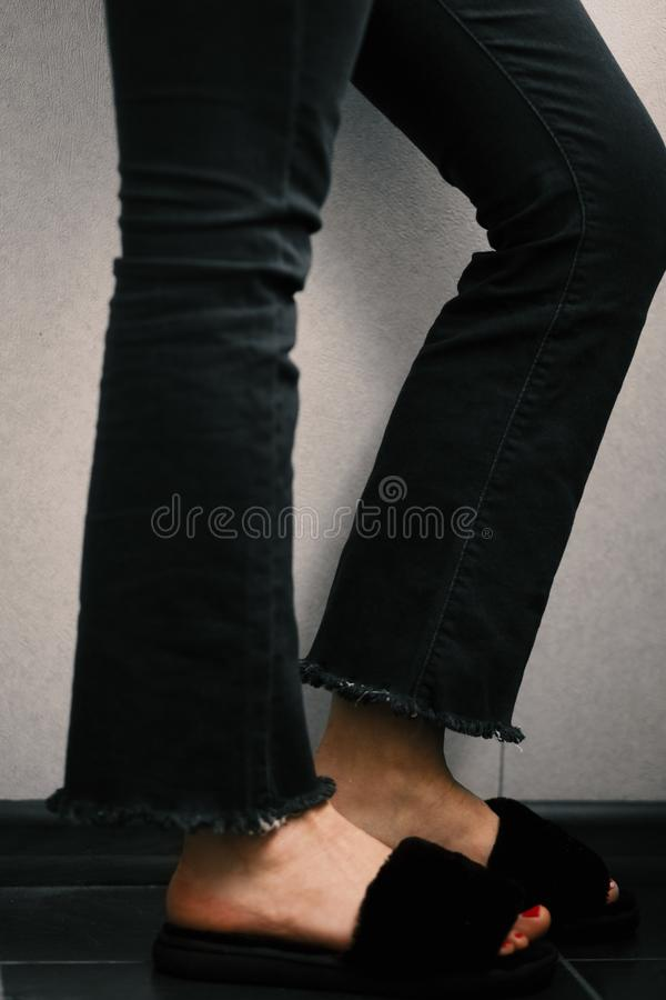 Vertical closeup shot of a person wearing black pants and slippers. A vertical closeup shot of a person wearing black pants and slippers stock photos