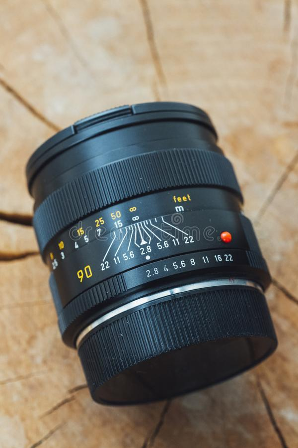 Vertical closeup shot of a professional camera lens on a wooden surface stock images