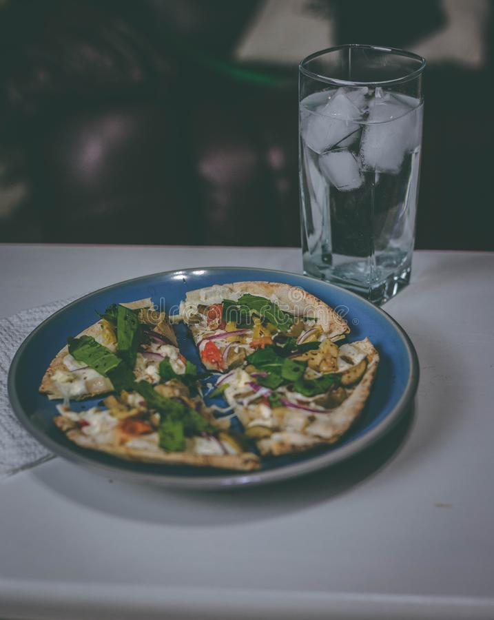 Vertical closeup shot of a table filled with a ice water glass and a plate filled with food stock photography