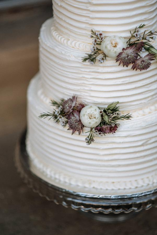 Vertical closeup shot of a three-layer wedding cake decorated with flowers on a silver platter. A vertical closeup shot of a three-layer wedding cake decorated stock photo