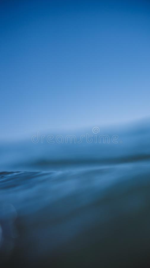 Vertical closeup shot of water with a blurred background. A vertical closeup shot of water with a blurred background stock photography