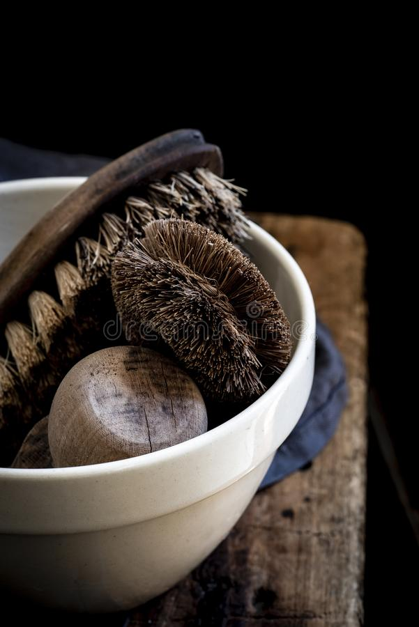 Vertical closeup shot of a white bowl with brushes for cleaning shoes on black background royalty free stock photography