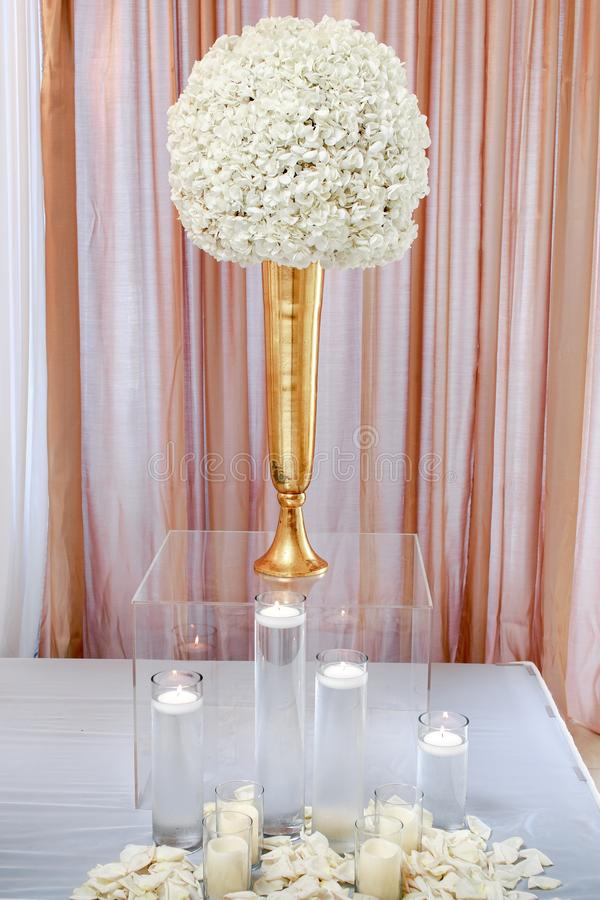 Vertical closeup shot of a white flower centerpiece on clear glass box with candles. A vertical closeup shot of a white flower centerpiece on clear glass box stock photography