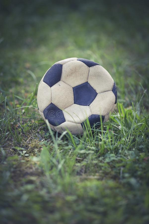 Vertical closeup shot of a worn-out soccer ball in a grassy field stock photo