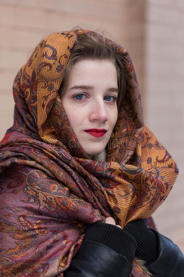 Young woman with blue eyes and red lipstick draping her head and shoulders in multicoloured shawl. Vertical closeup of stunning young woman with blue eyes and royalty free stock photos