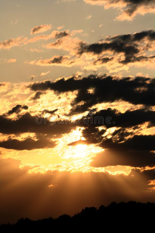 Vertical clouds with rays of sunlight shining through royalty free stock photos