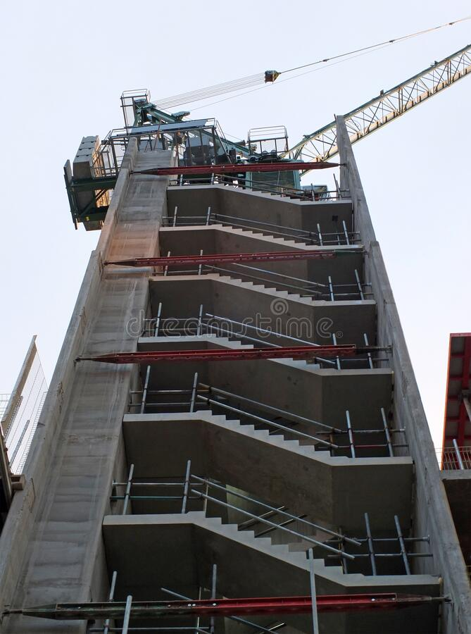 Vertical corner view of a crane on a construction site with a concrete framework against a blue sunlit sky stock photos
