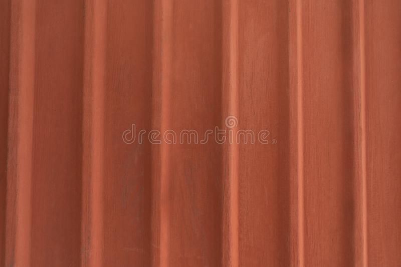 Vertical corrugated fence of matted orange metal sheets. stock photo