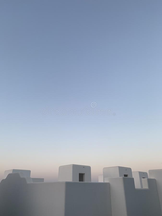 Vertical 3D illustration of white stone buildings with openings under a clear blue sky royalty free illustration