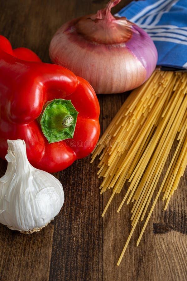 Vertical de la visión superior de los ingredientes para hacer los espaguetis, la pimienta roja, el ajo y la cebolla fotos de archivo