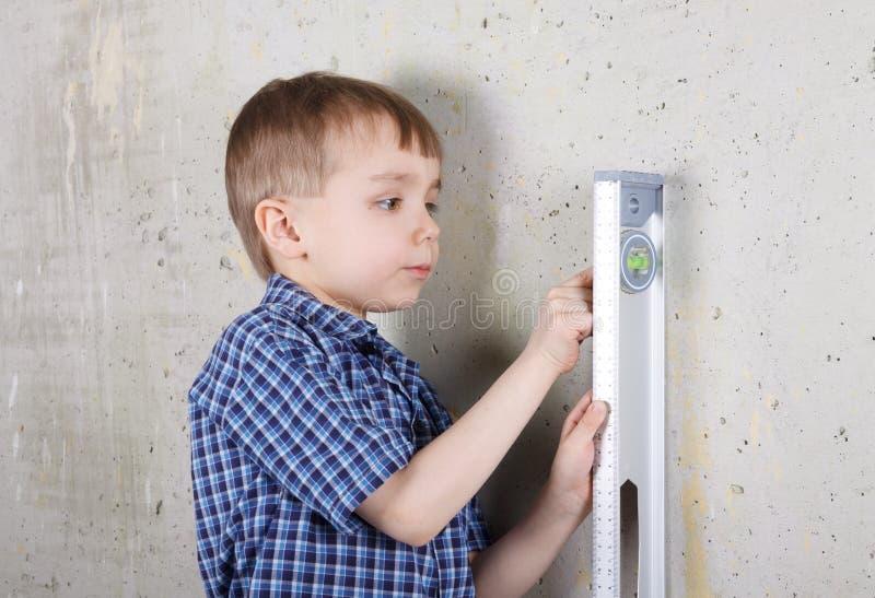 Vertical de medición del muchacho de la pared por el nivel imágenes de archivo libres de regalías