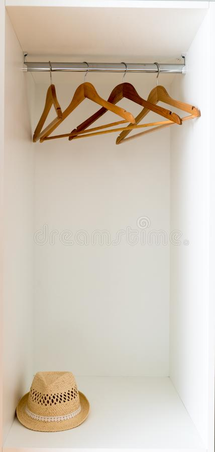 Free Vertical Detail View Of An Empty Coatrack In A White Wardrobe With A Straw Fedora Hat Stock Photography - 151582022