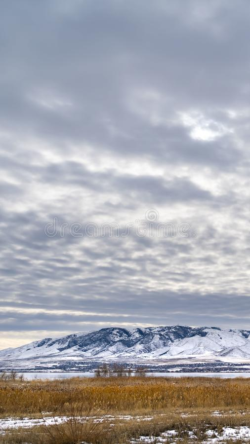 Vertical Dramatic sky filled with cottony clouds over a scenic landscape in winter. A lake and snow capped mountain cna be seen beyond the vast grassy terrain royalty free stock photos