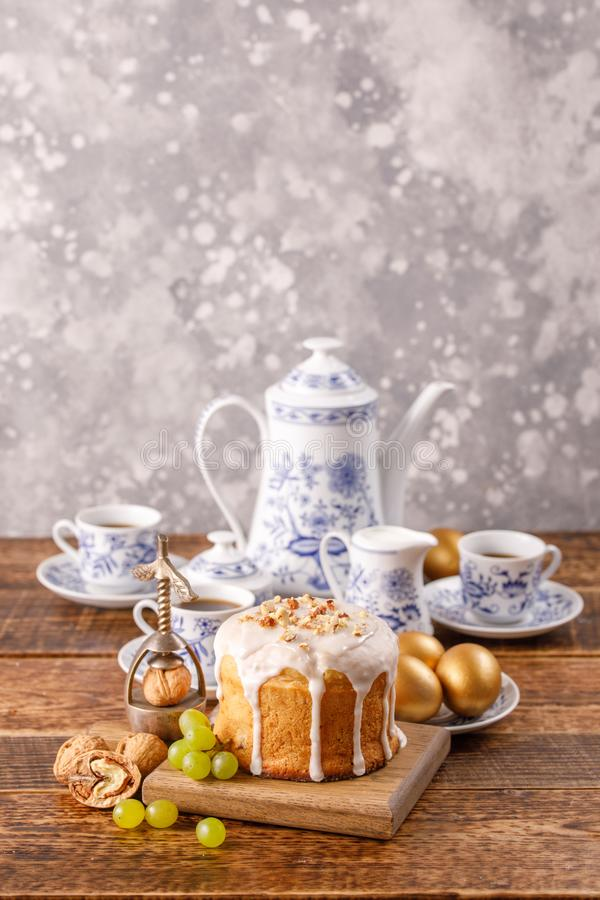 Vertical easter still life. A festive table with a home Easter cake, an ancient tea or coffee service and golden eggs. Easter card stock image