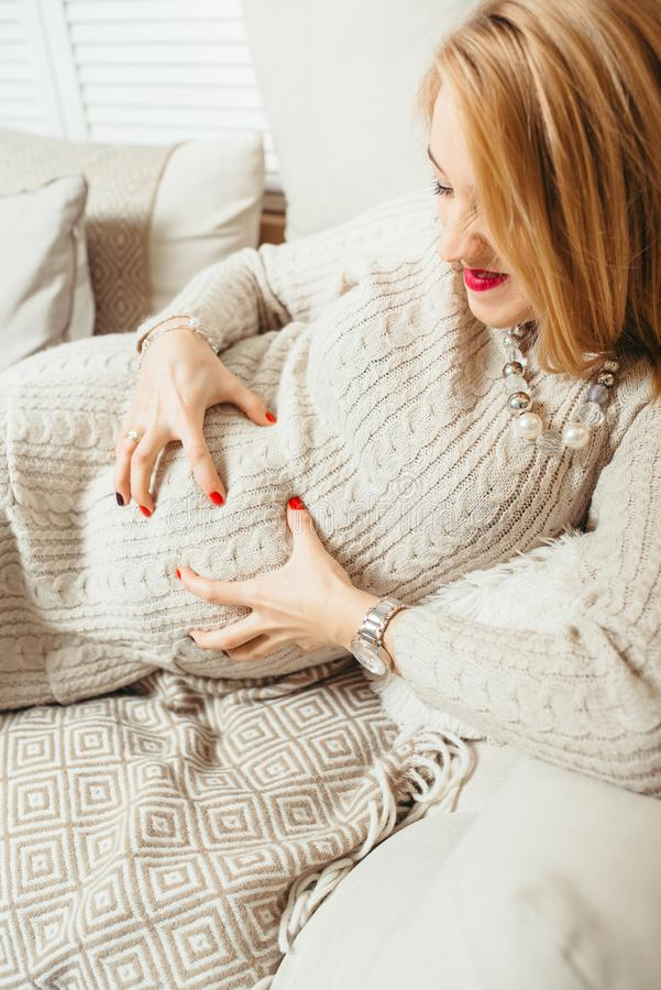 Vertical emotional portrait of the happy blonde pregnant woman resting on the couch while touching her tummy and making royalty free stock photography