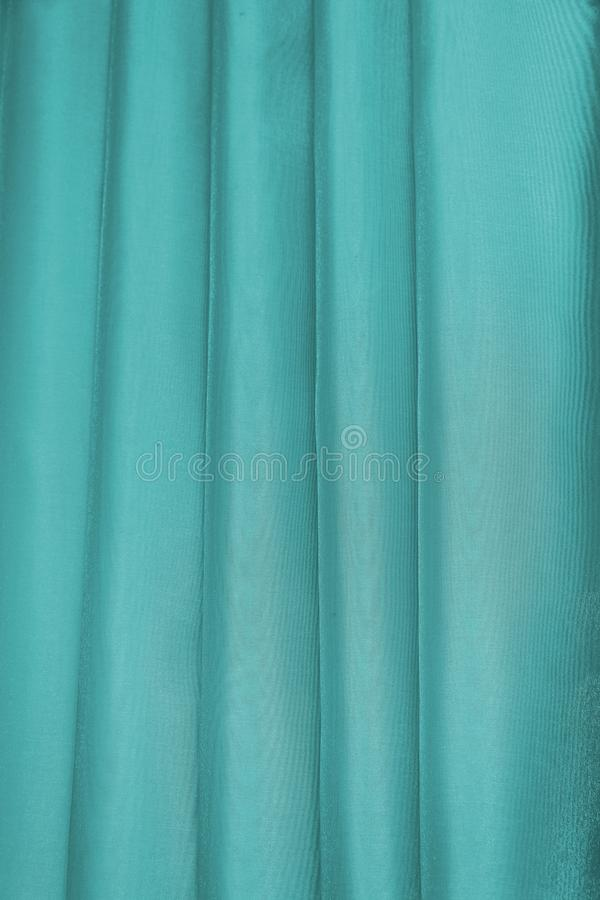 Vertical folds on green organza curtains. For background and design stock photo