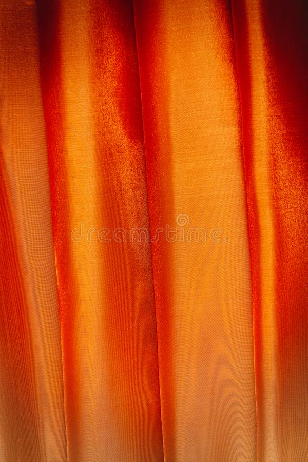 Vertical folds on orange organza curtains. For background and design royalty free stock images
