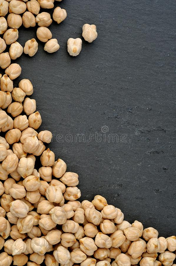 Vertical food background with raw chickpeas on black slate plate. Frame for text royalty free stock photos