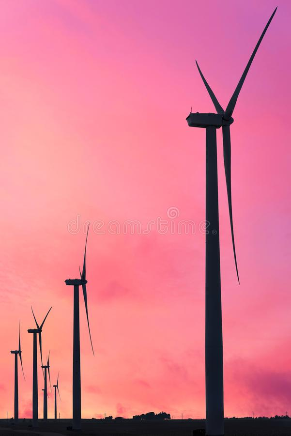 Vertical format of silhouettes of wind turbines on a farm in Iowa on a sunset sky. Background stock images