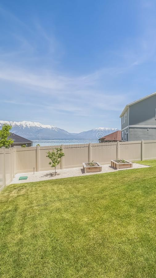 Vertical frame Backyard of a home with small tree and planting beds near the wooden fence. View of houses, lake, mountain, and sky can be seen from this grassy royalty free stock images