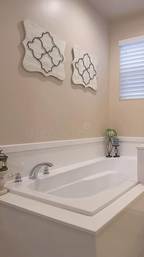 Vertical frame Bathroom interior with a polished built in bathtub and shower stall. Candles, wall decorations, and window with blinds can also be seen inside stock photos