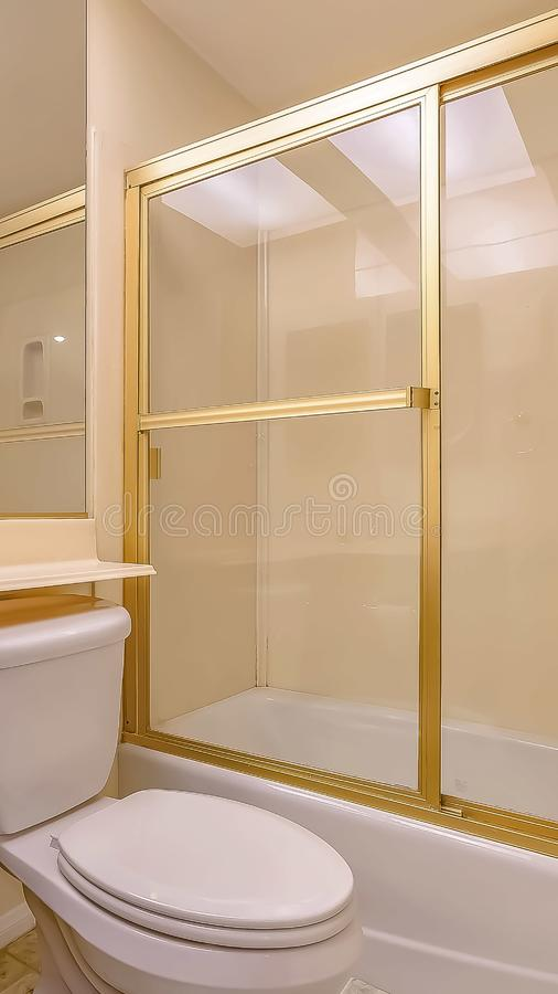 Vertical frame Bathroom interior with sink cabinet and toilet below the large mirror. The bathtub and shower stall has a glass door with golden frames stock image