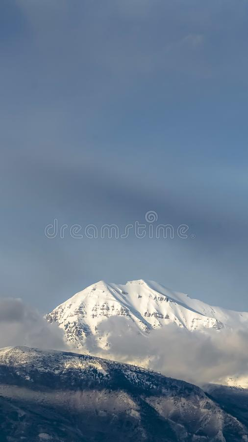 Vertical frame Beautiful view of a mountain with its peak covered with sunlit white snow. Gray clouds and blue sky can also be seen in this picturesque nature stock photography