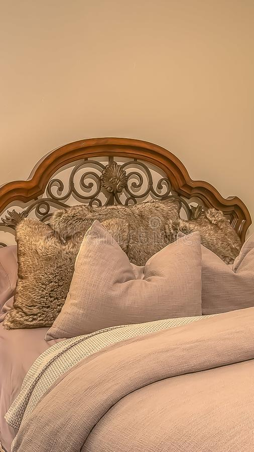 Vertical frame Bed with fluffy pillows against the wood and worught iron headboard. Small square windows and wooden side table with lamp can also be seen royalty free stock photography