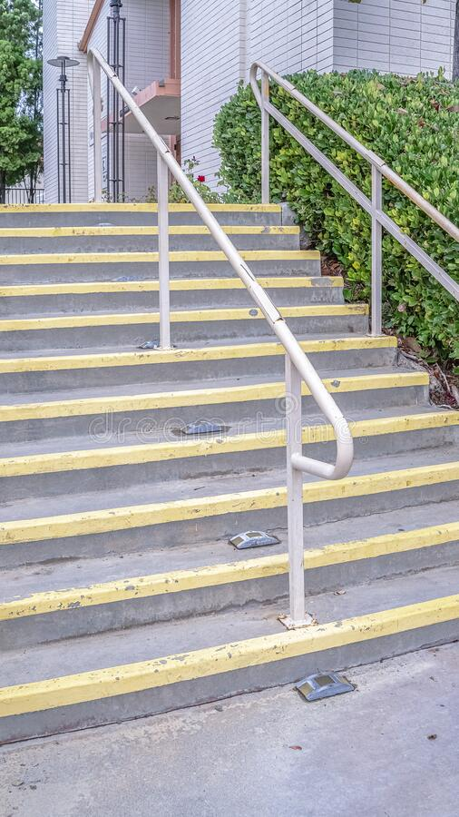 Vertical frame Cement entrance steps with yellow warning on a sunny day. Vertical frame Cement entrance steps with yellow warning painted on the treads viewed royalty free stock image