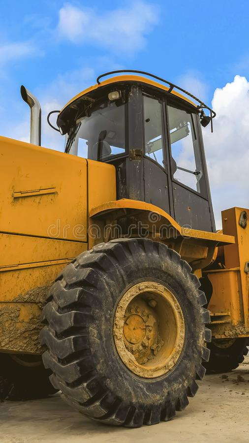 Vertical frame Close up of a dirty yellow loader with black rubber wheels and empty cab royalty free stock photos