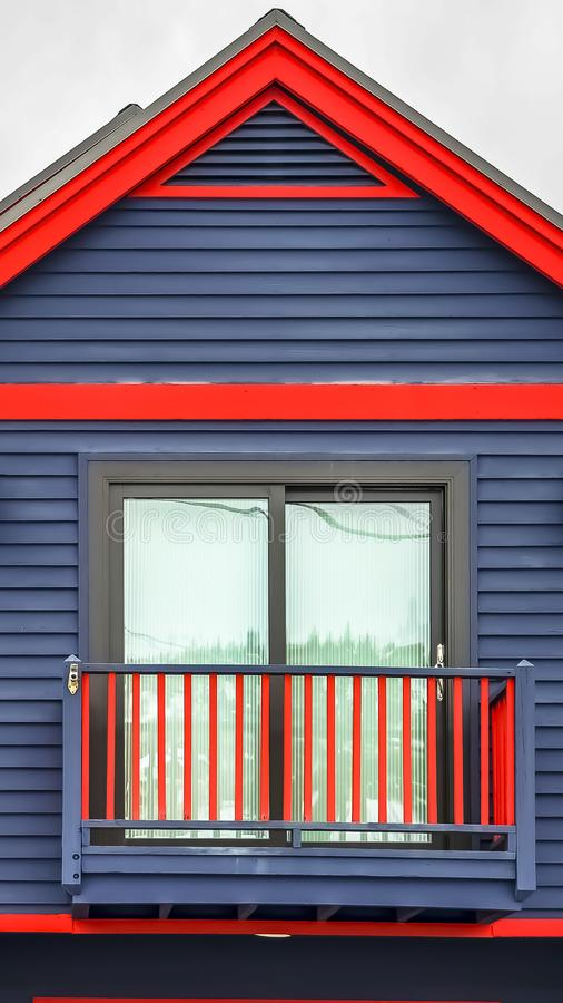 Vertical frame Close up of home exterior with vibrant blue wall red frames and small balcony. Cloudy sky and mountain covered with snow in winter cna be seen royalty free stock images