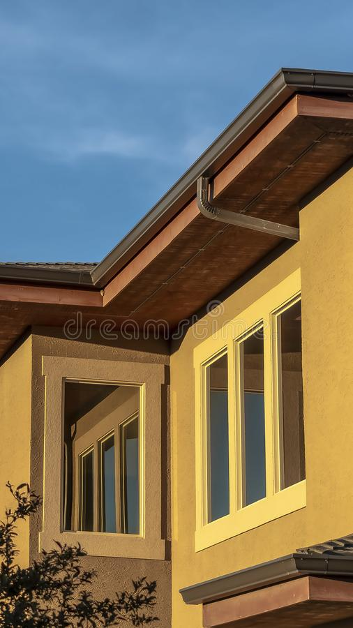Vertical frame Close up of a home upper storey exterior with trees and blue sky on a sunny day royalty free stock images