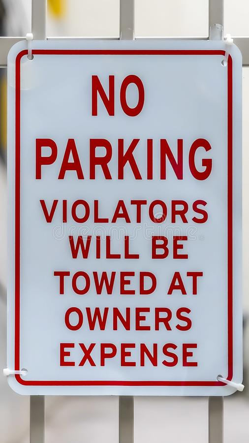 Vertical frame Close up of No Parking sign on awhite metal gate with building in the background royalty free stock photo