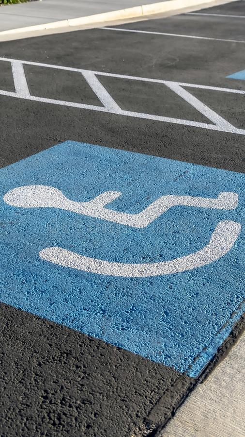 Vertical frame Close up of a person on a wheelchair icon painted on the black pavement royalty free stock photo