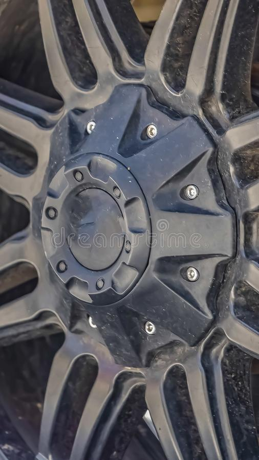 Vertical frame Close up view of the black rubber wheel of a vehicle. The wheel has a black rim and the brake pad cna be seen through the black radial spokes stock image